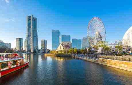 Yokohyama Japan, Red boat floating down the river with Yokohama in the background